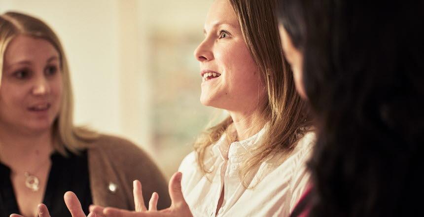 Tre kvinnor sitter bredvid varandra och pratar