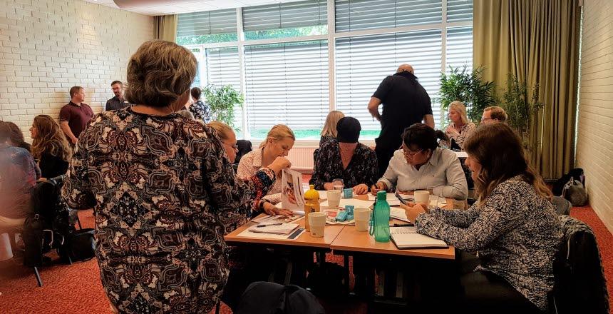 Människor som sitter och arbetar i ett konferensrum