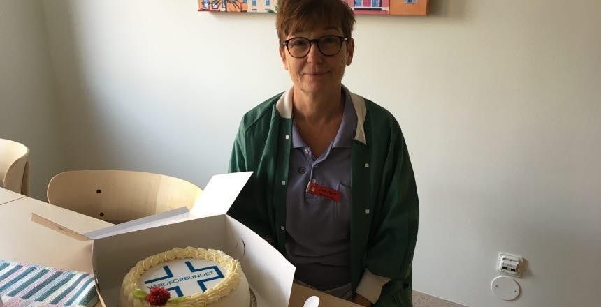 En kvinna sitter vid ett bord med en tårta framför sig. Hon arbetar på medicinmottagningen i Sundsvall.