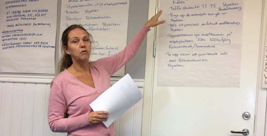 En kvinna står och pekar och pratar om en text som finns skrivet på ett blädderblockspapper som sitter på väggen.