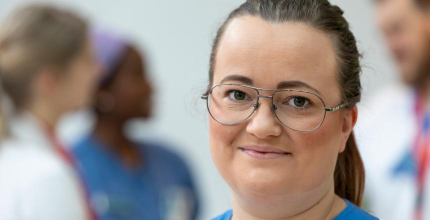 I fokus en kvinna med glasögon och mörkt hår samlat i en svans. I bakgrunden skymtar 3 personer i sjukhusarbetskläder.
