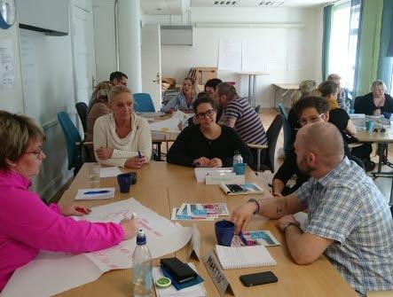 Människor som sitter kring bord på en utbildning och diskuterar, en person skriver på ett blädderblockspapper