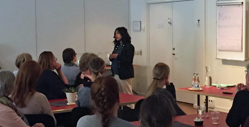 En kvinna med mörkt hår står inför en grupp och föreläser