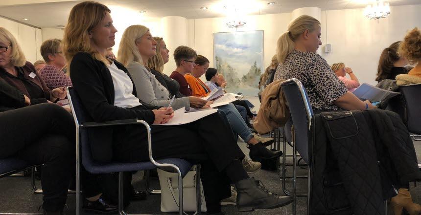 Folk som sitter i biosittning i ett konferensrum.