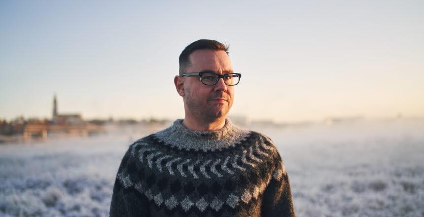 Man i glasögon och ulltröja i vinterlandskap i solnedgång