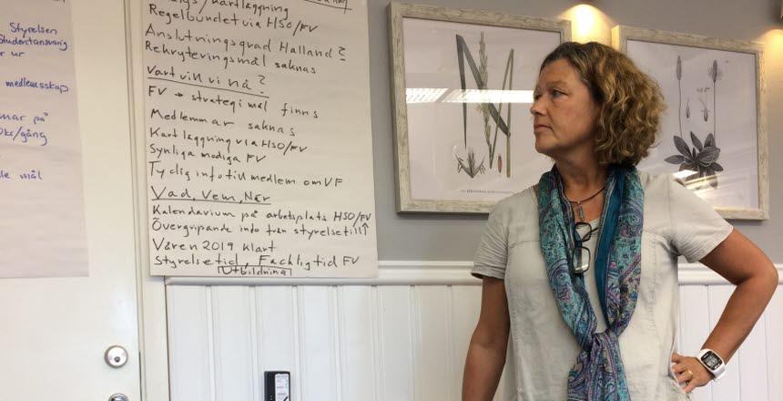En kvinna i vit klänning, med en schal hängande runt halsen står och lutar sig på ett bord och tittar på anteckningar från ett stort blädderblockspapper som hänger på väggen.