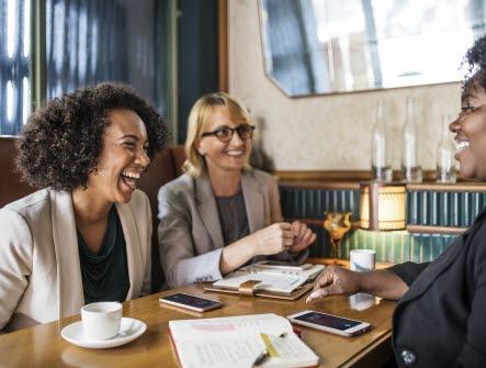 tre kvinnor som sitter vid ett bord och ler