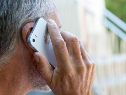 Man håller mobiltelefon mot höger öra. Bilden är tagen bakifrån. Mannen har gråsprängt hår och lite skäggstubb.