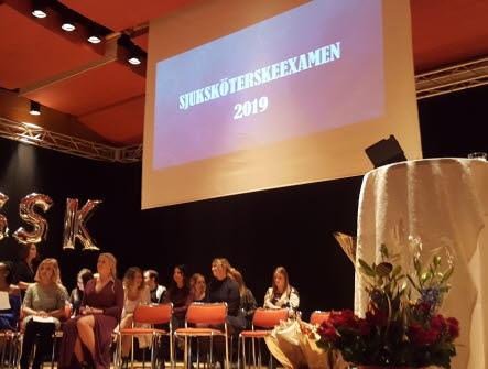 Nyutexaminerade sjuksköterskor som sitter på stolar på en scen. I bakgrunden finns det ballonger med bokstäverna SSK och på en skärm står det sjuksköterskeexamen 2019