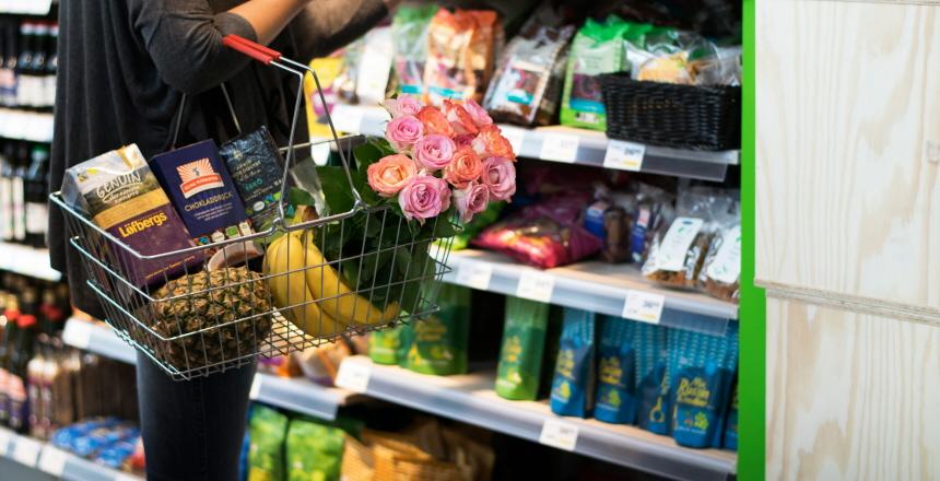 Kvinna i butik med fair trade-varor i varukorg