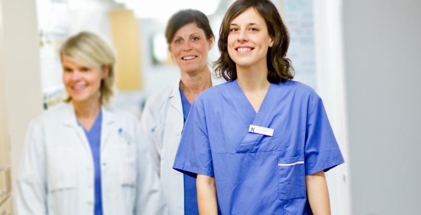 Tre sjukvårdsklädda kvinnor som kommer gående i en korridor och ler