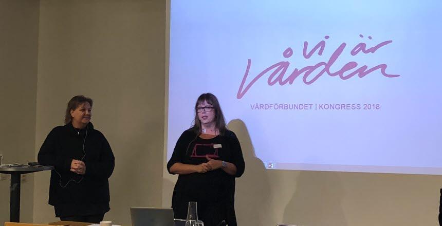 Två kvinnor står bredvid varandra och pratar inför publik. På skärmen bakom dom står det en text - Vi är vården.