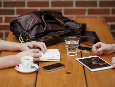 Två personer sitter vid bord och har möte, väska, vatten, glas, kaffe, mobil, telefon, anteckning, penna, hand, händer, skriva, planering, papper, ipad, padda, planera