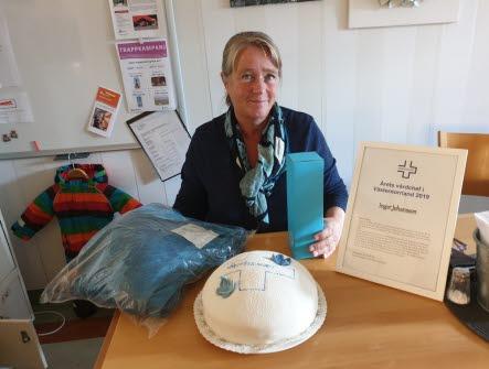 Årets vårdchef Inger Johansson sitter vid ett bord med ett diplom och en tårta framför sig