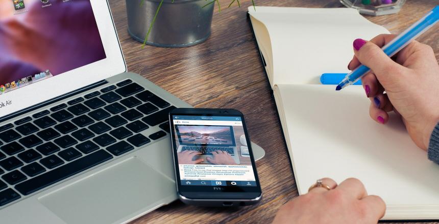Kvinna skriver och har mobil och dator framför sig