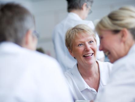 Tre sjuksköterskor sitter runt ett bord och pratar och skrattar på Boo Vårdcentral