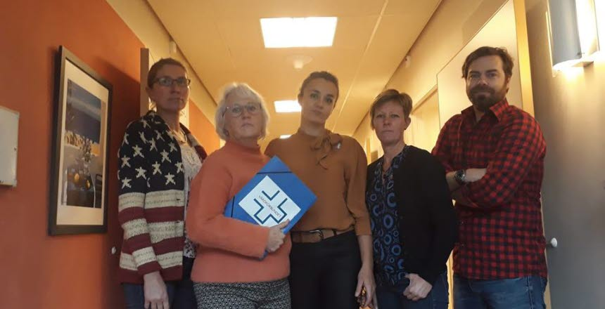 Fem personer står bredvid varandra i en korridor, fyra kvinnor och en man. Dom ser allvarliga ut.