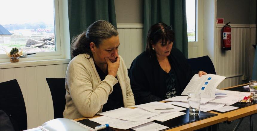 Två kvinnor sitter vid ett bord och bläddrar i papper och ser fundersamma ut.