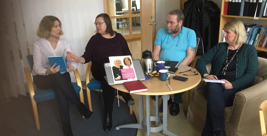Fyra personer, tre kvinnor och en man sitter vid ett runt bord och diskuterar. På bordet finns det en dator, en termos och kaffekoppar.
