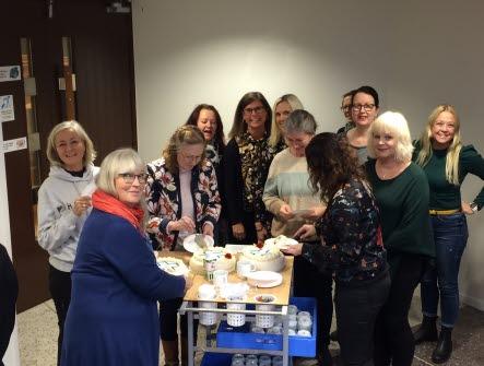 Ett gäng med skolsköterskor står kring ett bord med tårta och kaffe på