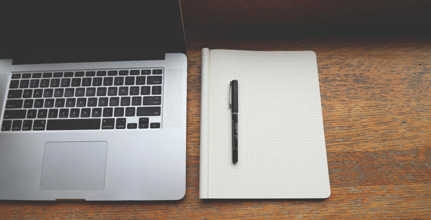 En dator, ett block och en penna