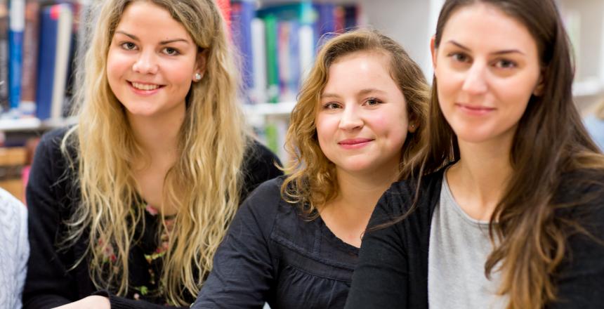 Tre unga tjejer sitter på rad och ler mot kameran