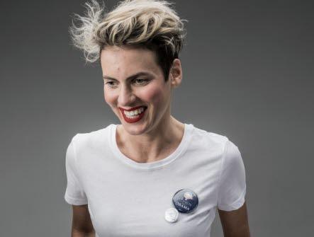Halvkroppsbild på leende, blond kortklippt kvinna med röda läppar. Klädd i vit t-shirt. Grå bakgrund.