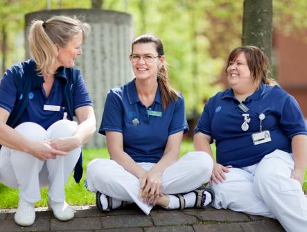 Tre leende kvinnliga sjuksköterskor med blå tröja och vita byxor sitter i gräset.