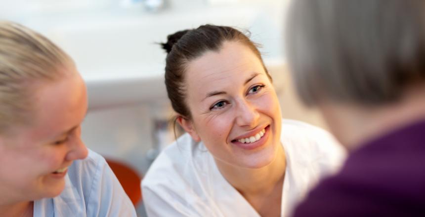 Sjuksköterskor på kärlkirurgiska avdelningen på SÖS samtalar med patient. Sjuksköterskorna ler och ser glada ut.