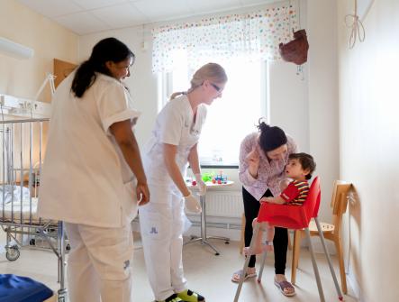 Mamma och barn tillsammans med sjuksköterskor i ett rum på barnavdelningen på SÖS. Barnet sitter i en röd barnstol.
