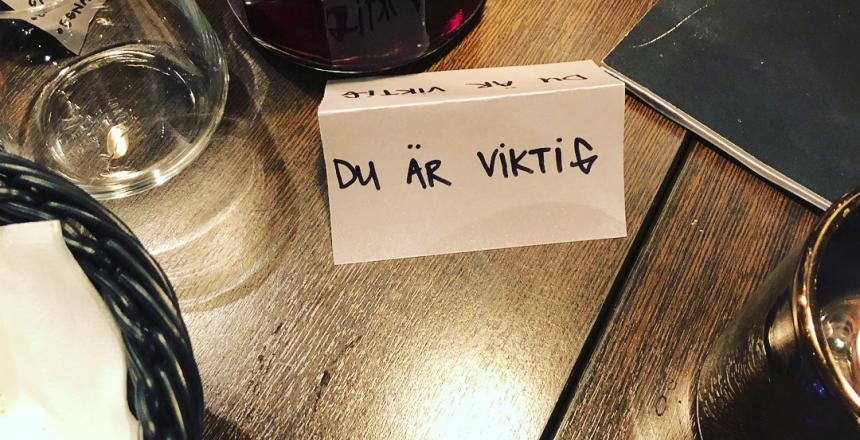 Närbild på ett dukat bord där man ser ett glas, någon lykta och en brödkorg. Det finns även en lapp som det står Du är viktigt på.