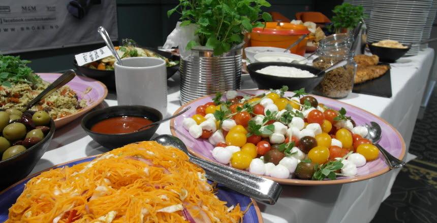 Buffébord uppdukat med stora fat med sallader och diverse skålar med oliver och såser.