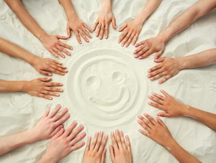 En glad gubbe som är ritad i sand och runt den är en massa händer.