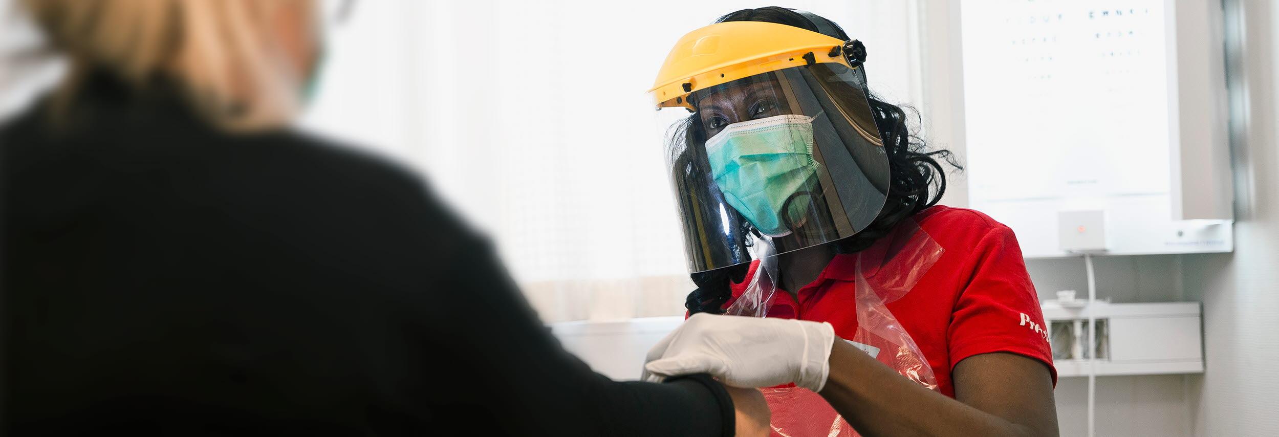 Kvinnlig intensivvårdssjuksköterska klädd i full skyddsutrustning för att inte smittas av covid-19